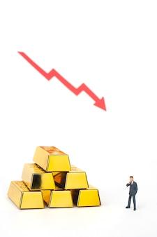 Uomo d'affari in miniatura con pila di lingotti d'oro su sfondo bianco