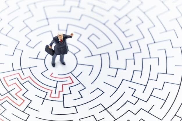 Uomo d'affari in miniatura in piedi sul centro del labirinto utilizzando