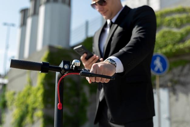 Uomo d'affari in piedi accanto a uno scooter elettrico