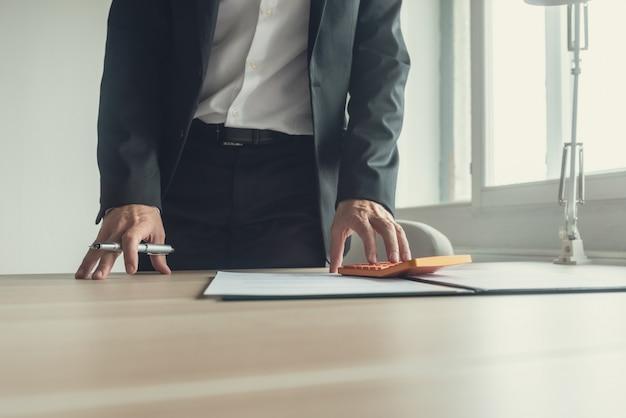 Uomo d'affari in piedi alla sua scrivania