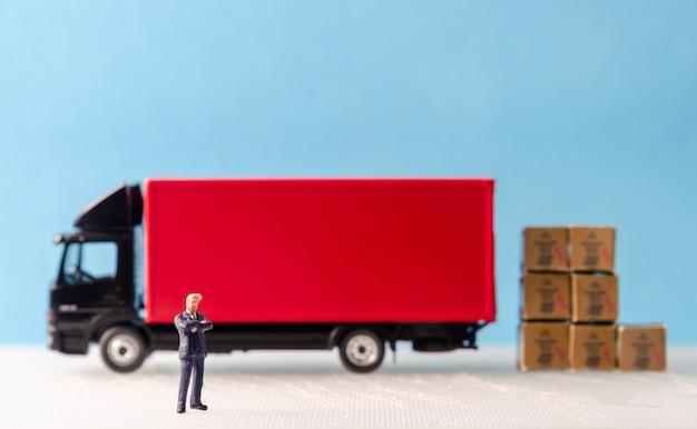Uomo d'affari in piedi davanti alla flotta di camion cargo