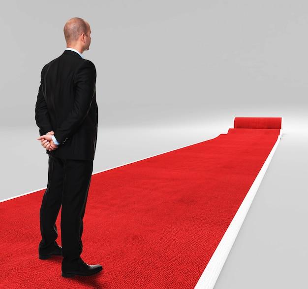 Uomo d'affari in piedi sul tappeto rosso