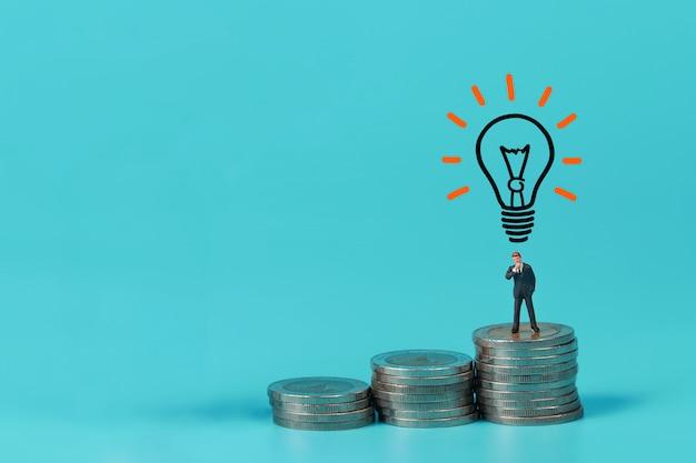 Uomo d'affari in piedi sulla moneta impilabile podio con lampadina