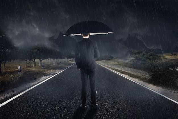 Uomo d'affari in pioggia con in piedi ombrello