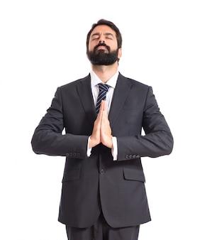 Uomo d'affari in posizione zen su sfondo bianco