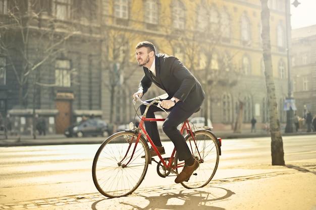 Uomo d'affari in sella a una bicicletta