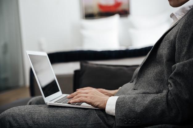 Uomo d'affari in tuta con un computer portatile in grembo