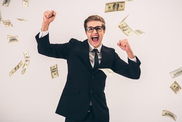 Uomo d'affari in tuta e occhiali con la caduta delle bollette