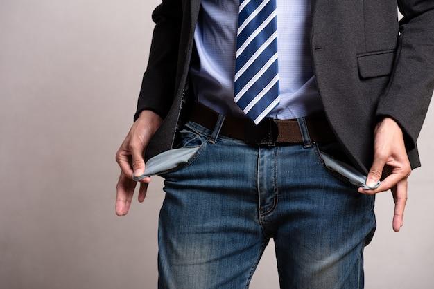 Uomo d'affari in tuta mostrando le sue tasche vuote. difficoltà finanziarie