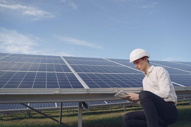 Uomo d'affari in un casco bianco vicino alla batteria solare