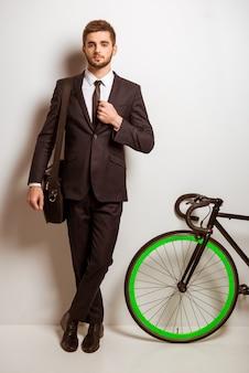 Uomo d'affari in un tailleur con una bicicletta.