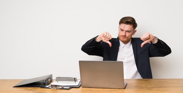 Uomo d'affari in un ufficio che mostra pollice giù
