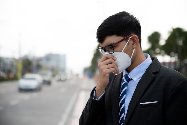 Uomo d'affari in un vestito che indossa maschera protettiva e tosse