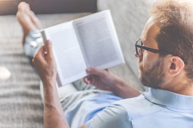 Uomo d'affari in vestiti ed occhiali che legge un libro