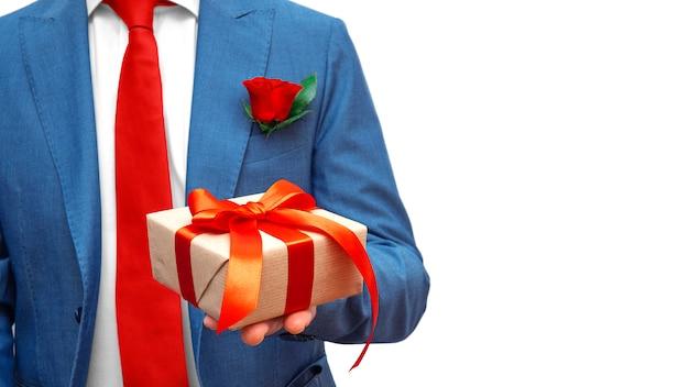 Uomo d'affari in vestito blu e legame rosso con il contenitore e la rosa di regalo della carta del mestiere isolati. l'uomo d'affari presenta un premio. copia spazio. pubblicità, vendita, sconto.