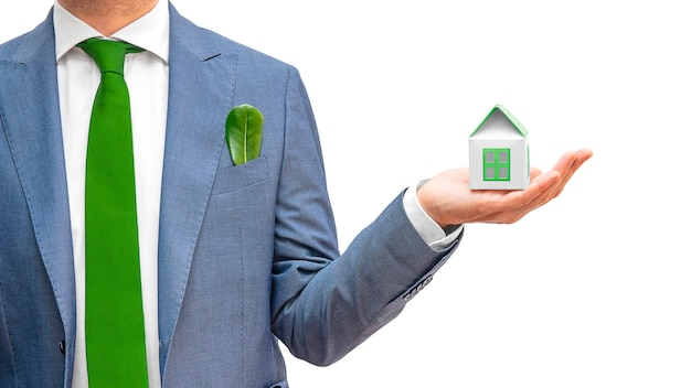 Uomo d'affari in vestito blu, legame verde che giudica casa astuta verde isolata. consapevolezza e consapevolezza ambientale, concetto eco-compatibile. copia spazio