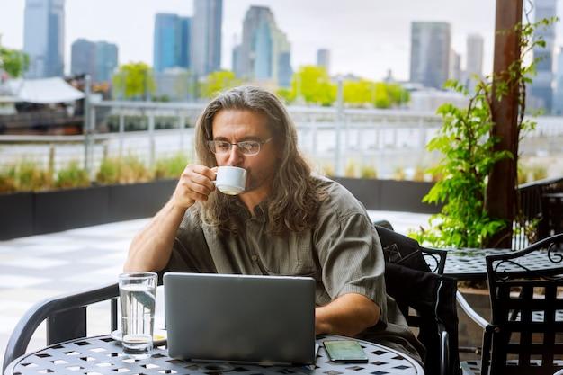 Uomo d'affari in viaggio, lavorando a new york city, tenendo la tazza di caffè, lavorando sul portatile
