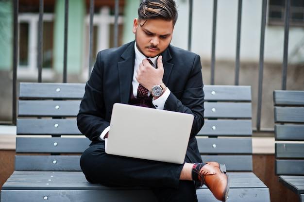 Uomo d'affari indiano alla moda nell'usura convenzionale che si siede sul banco con il computer portatile.