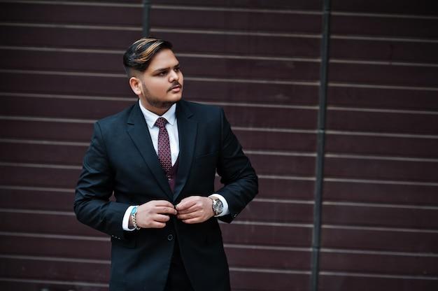 Uomo d'affari indiano alla moda nell'usura convenzionale che sta contro l'otturatore marrone.