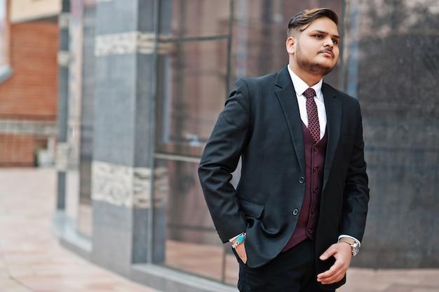 Uomo d'affari indiano alla moda nell'usura convenzionale che sta contro le finestre nel centro di affari.