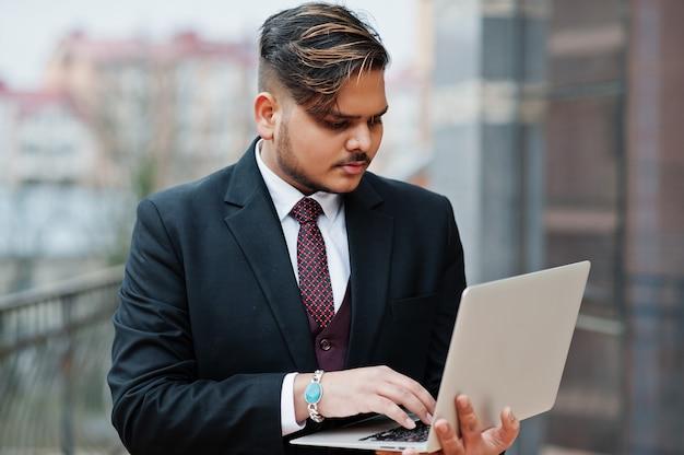 Uomo d'affari indiano alla moda nell'usura convenzionale con il computer portatile sulle mani che stanno contro le finestre nel centro di affari.