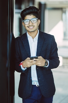 Uomo d'affari indiano asiatico che manda un sms facendo uso dello smartphone mentre stando nell'ufficio
