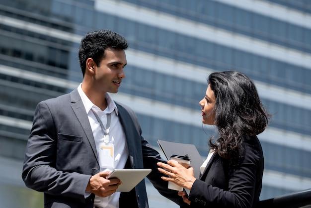 Uomo d'affari indiano che incontra donna di affari all'aperto nella città