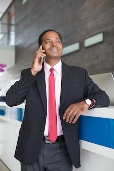 Uomo d'affari indiano chiamata sul telefono alla reception