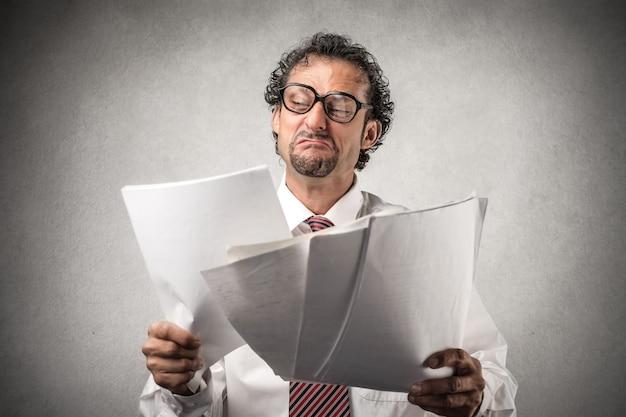 Uomo d'affari infelice che tiene alcuni documenti