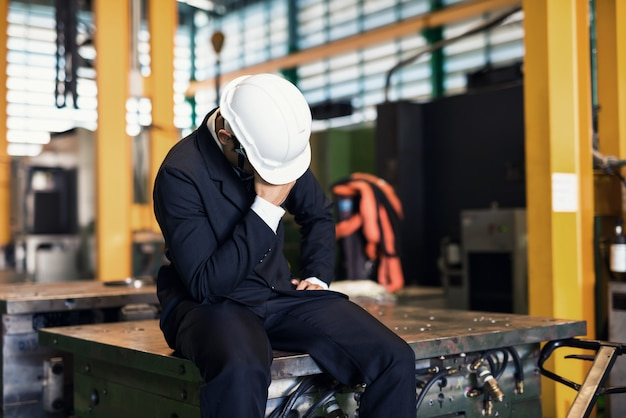 Uomo d'affari infornato triste in fabbrica