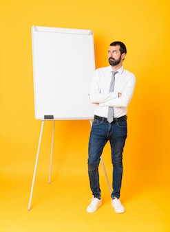 Uomo d'affari integrale che dà una presentazione sul bordo bianco sopra la parete gialla isolata con l'espressione confusa del fronte
