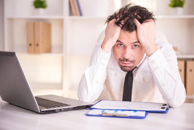 Uomo d'affari invecchiato centrale frustrato che si siede all'ufficio.