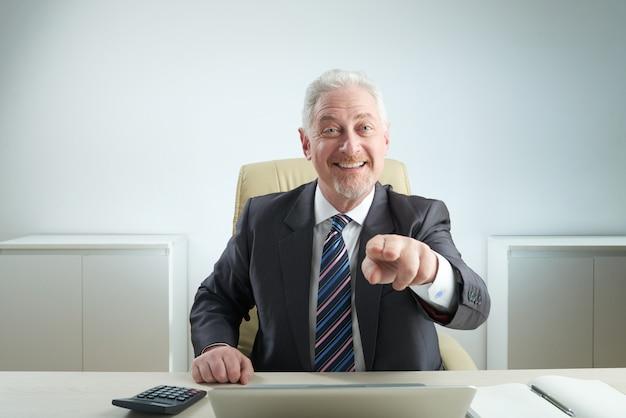 Uomo d'affari invecchiato che indica alla macchina fotografica