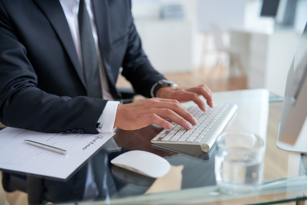 Uomo d'affari irriconoscibile che scrive sulla tastiera in ufficio
