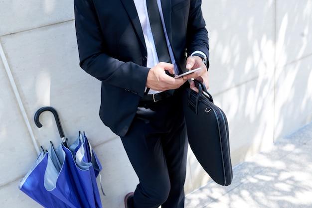 Uomo d'affari irriconoscibile con la cartella e l'ombrello che stanno all'aperto e che per mezzo dello smartphone