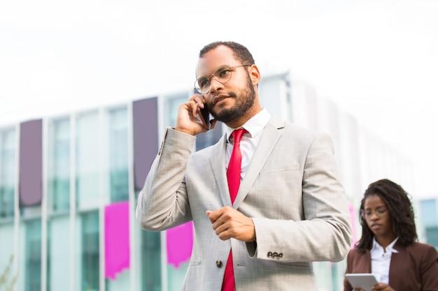 Uomo d'affari latino serio che parla sul cellulare