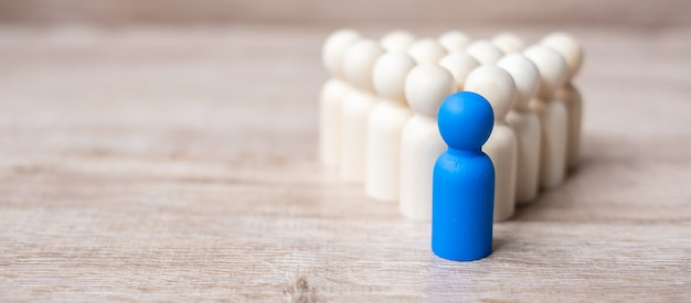 Uomo d'affari leader blu con folla di uomini in legno. leadership, business, team, lavoro di squadra e gestione delle risorse umane