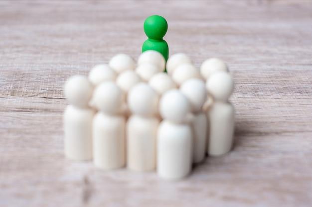 Uomo d'affari leader verde con folla di uomini in legno. leadership, business, team, lavoro di squadra e concetto di gestione delle risorse umane