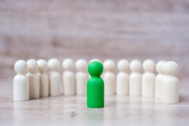 Uomo d'affari leader verde con folla di uomini in legno. leadership, business, team, lavoro di squadra e gestione delle risorse umane