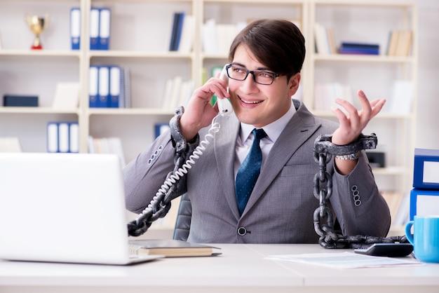 Uomo d'affari legato con catene al suo lavoro