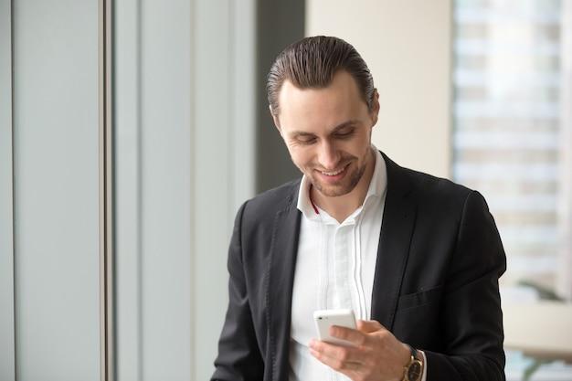Uomo d'affari leggere e inviare messaggi sul telefono