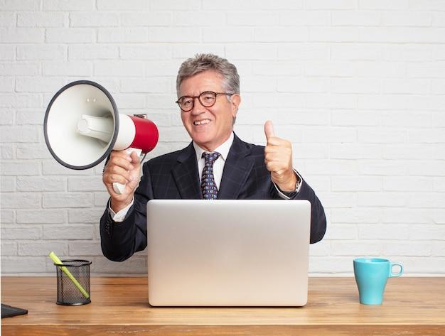 Uomo d'affari maggiore che lavora con il suo computer portatile e un megafono