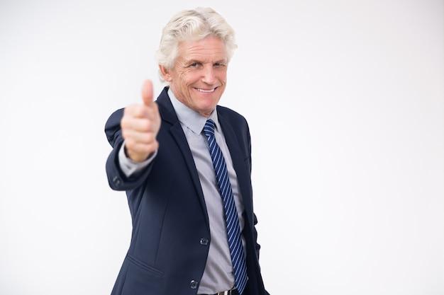Uomo d'affari maggiore che mostra i pollici di successo fino