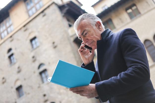 Uomo d'affari maggiore che parla su uno smartphone