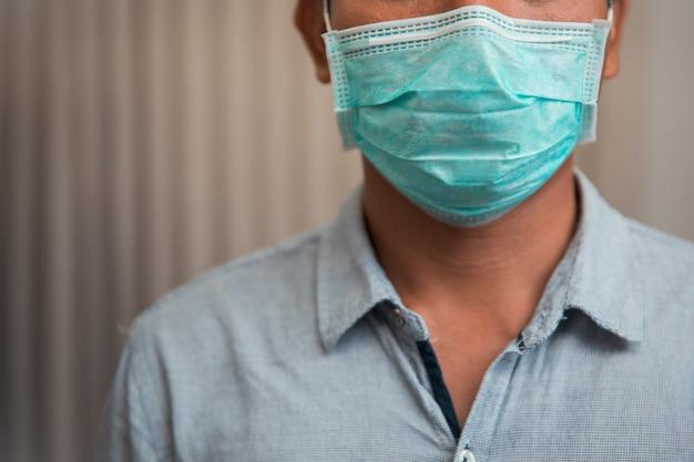 Uomo d'affari maschio che chiude la maschera protettiva a causa di malattia e tosse