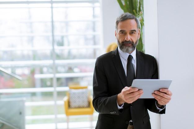 Uomo d'affari maturo bello con la compressa nel funzionamento, nella lettura o nella ricerca dell'ufficio qualcosa