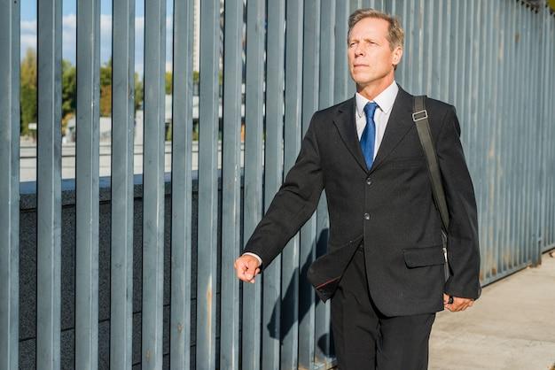 Uomo d'affari maturo che cammina nel marciapiede