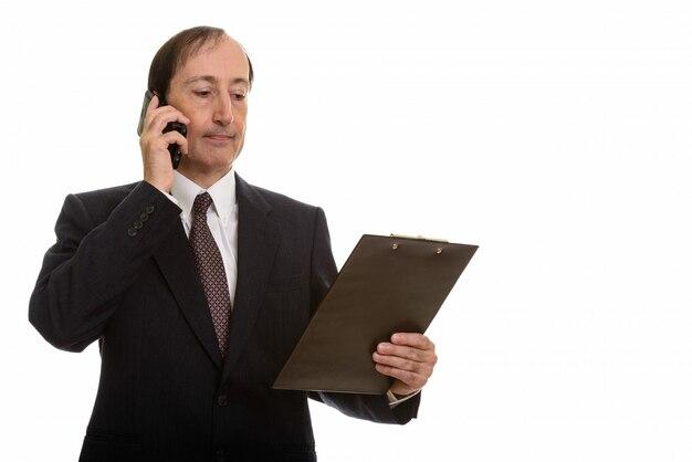 Uomo d'affari maturo che parla sul telefono cellulare mentre