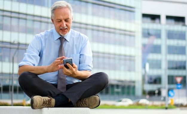 Uomo d'affari maturo che usando la sua seduta all'aperto del suo smartphone su un banco