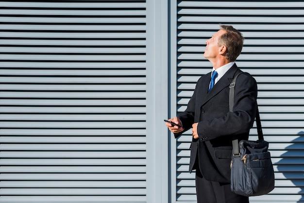 Uomo d'affari maturo con il telefono cellulare che osserva in su